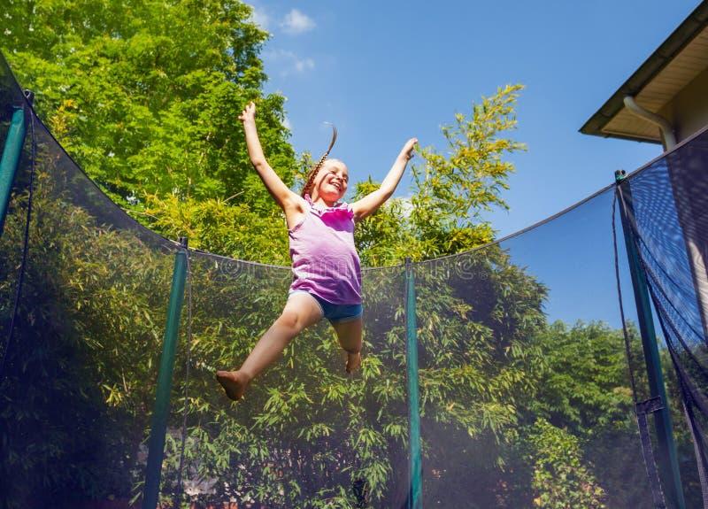 Χαρούμενο κορίτσι που αναπηδά γύρω από ένα τραμπολίνο υπαίθρια στοκ φωτογραφία