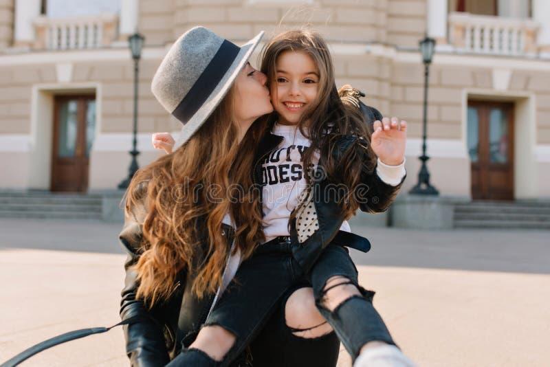 Χαρούμενο κορίτσι brunette με την καλή έκφραση προσώπου στα μοντέρνα τζιν με τις τρύπες που κάθεται στο γόνατο και το γέλιο των m στοκ φωτογραφίες