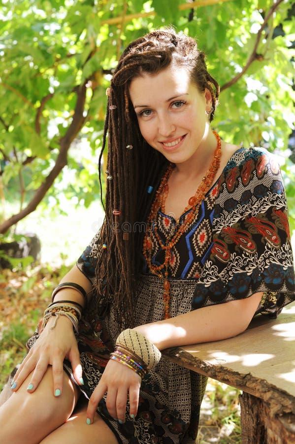 Χαρούμενο νέο πορτρέτο γυναικών με τα dreadlocks που ντύνονται στο φόρεμα ύφους boho και το περιδέραιο, ηλιόλουστος υπαίθριος στοκ εικόνες