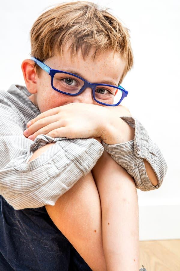 Χαρούμενο παιδί που κρύβεται γελώντας στα γόνατά του και τα χέρια του για νωθρότητα στοκ εικόνα
