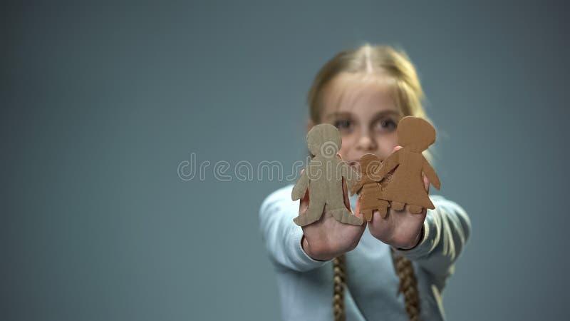 Χαρούμενο παιδί που παρουσιάζει οικογένεια εγγράφου στη κάμερα, ορφανός που βρίσκει τους γονείς και το σπίτι στοκ φωτογραφίες