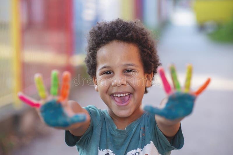 Χαρούμενο πεντάχρονο αγόρι με τα χέρια ζωγραφισμένα σε πολύχρωμα χρώματα στοκ εικόνες με δικαίωμα ελεύθερης χρήσης