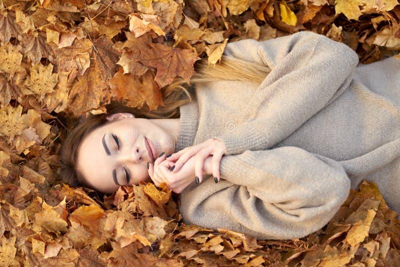 Χαρούμενο χαμογελαστό χαριτωμένο κορίτσι με κλειστά μάτια να λιώνει στα φθινοπωρινά φύλλα και να το απολαμβάνει, να κρατά το πρόσ στοκ εικόνα με δικαίωμα ελεύθερης χρήσης