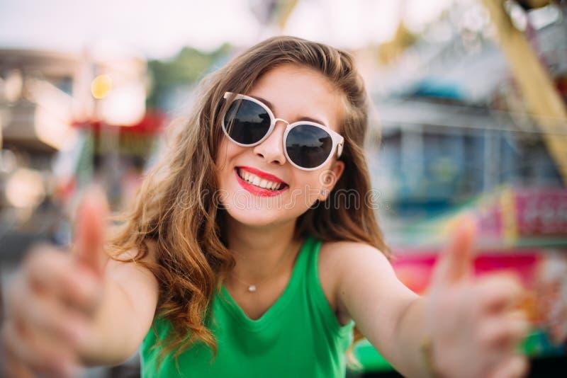 Χαρούμενο χαμογελώντας κορίτσι στα ρόδινα γυαλιά ηλίου που κάνει selfie μπροστά από το ιπποδρόμιο Υπαίθριο πορτρέτο της χαριτωμέν στοκ φωτογραφίες με δικαίωμα ελεύθερης χρήσης