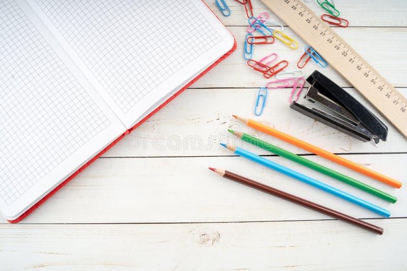 Χαρτικά που τοποθετούνται διάφορα στον πίνακα ξυλείας Άνωθεν χρωματισμένα μολύβια και ανοικτό σημειωματάριο που τακτοποιούνται στ στοκ φωτογραφία
