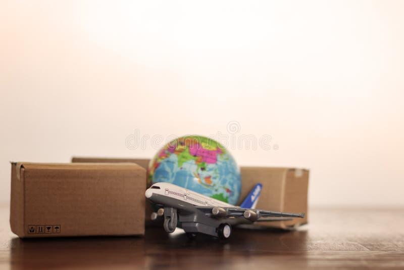 Χαρτοκιβώτια με τη σφαίρα αεροπλάνων και γης Σφαιρικές διοικητικές μέριμνες, ναυτιλία και παγκόσμια επιχειρησιακή έννοια παράδοση στοκ φωτογραφία με δικαίωμα ελεύθερης χρήσης