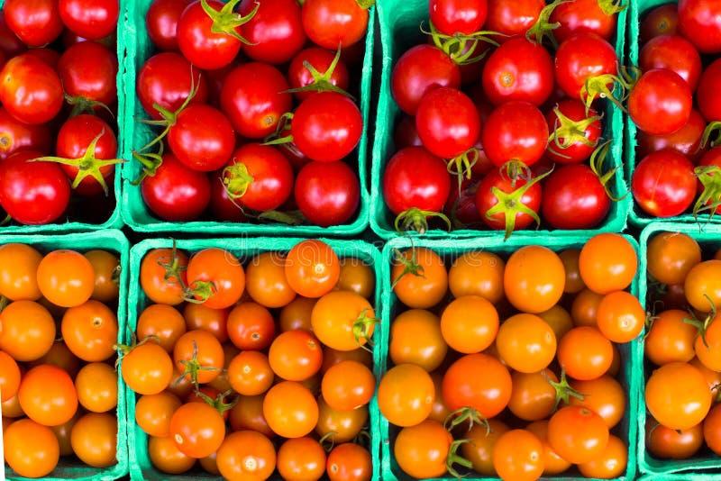Χαρτοκιβώτια της πορτοκαλιάς και κόκκινης ποικιλίας των ώριμων ντοματών κερασιών στοκ φωτογραφία με δικαίωμα ελεύθερης χρήσης