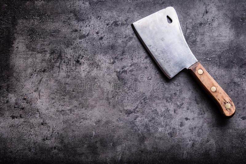 χασάπης Οι εκλεκτής ποιότητας μπαλτάδες κρέατος χασάπηδων με την πετσέτα υφασμάτων στη σκοτεινή συγκεκριμένη ή ξύλινη κουζίνα επι στοκ φωτογραφία με δικαίωμα ελεύθερης χρήσης