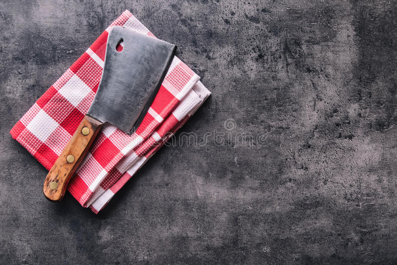 χασάπης Οι εκλεκτής ποιότητας μπαλτάδες κρέατος χασάπηδων με την πετσέτα υφασμάτων στη σκοτεινή συγκεκριμένη ή ξύλινη κουζίνα επι στοκ φωτογραφία