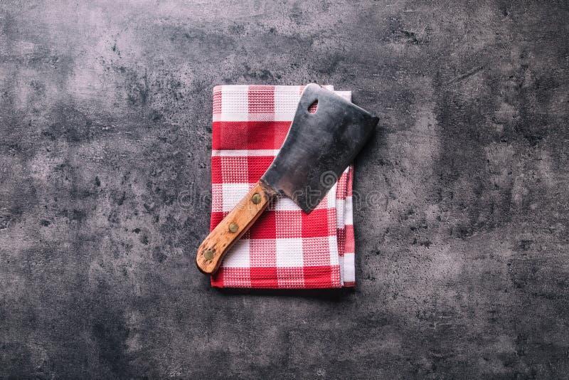 χασάπης Οι εκλεκτής ποιότητας μπαλτάδες κρέατος χασάπηδων με την πετσέτα υφασμάτων στη σκοτεινή συγκεκριμένη ή ξύλινη κουζίνα επι στοκ φωτογραφίες