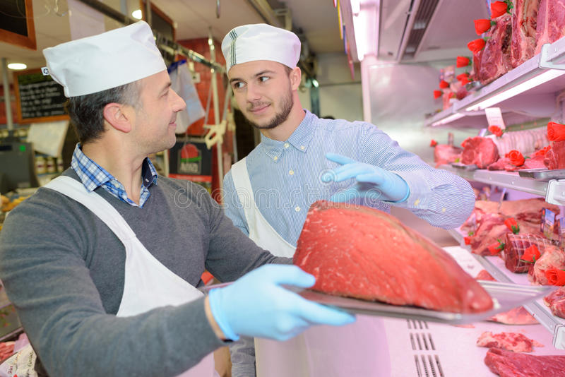 Χασάπης που κρατά το μεγάλο κοινό κρέας στο δίσκο στοκ εικόνα με δικαίωμα ελεύθερης χρήσης