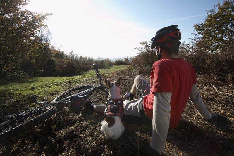 Χαλάρωση ατόμων και σκυλιών εκτός από το ποδήλατο βουνών στην επαρχία στοκ φωτογραφία με δικαίωμα ελεύθερης χρήσης