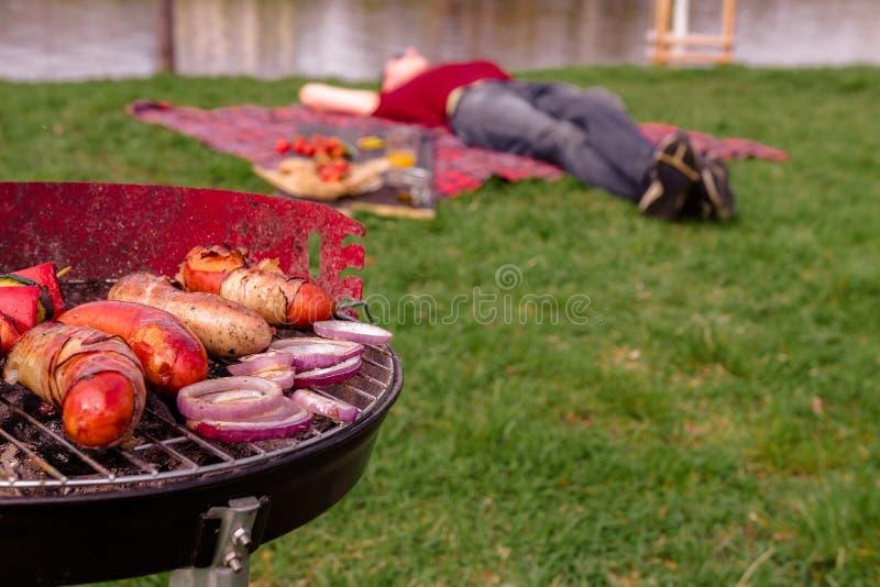 Χαλάρωση ατόμων στο πάρκο και κατοχή του μεσημεριανού γεύματος σχαρών Σχάρα με τη διάφορη εύγευστη υπαίθρια, εκλεκτική εστίαση σχ στοκ φωτογραφία
