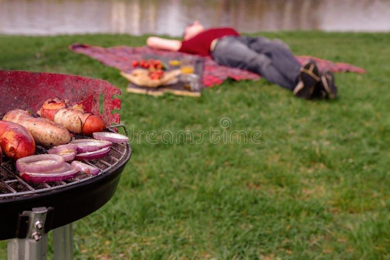 Χαλάρωση ατόμων στο πάρκο και κατοχή του μεσημεριανού γεύματος σχαρών Σχάρα με τη διάφορη εύγευστη υπαίθρια, εκλεκτική εστίαση σχ στοκ εικόνες