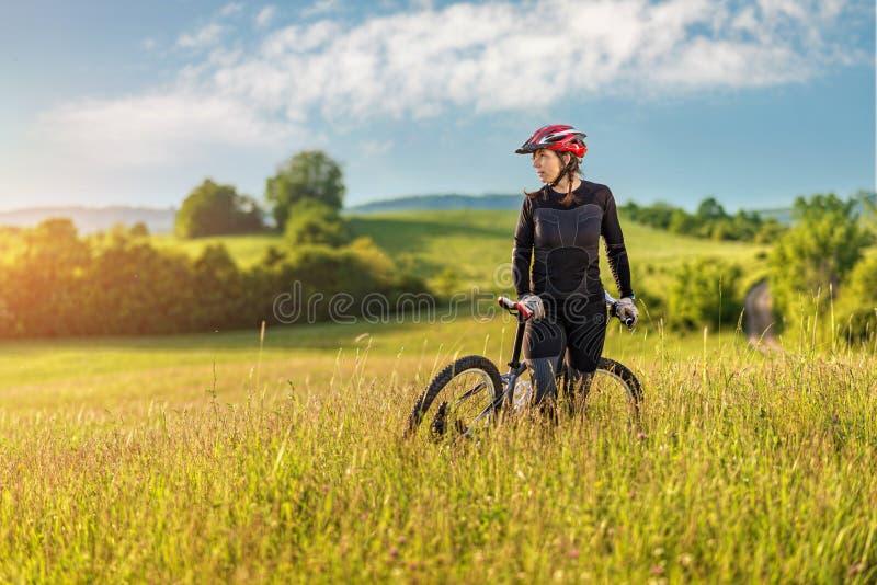 Χαλάρωση γυναικών αθλητικών ποδηλάτων σε ένα λιβάδι, όμορφο τοπίο στοκ εικόνα
