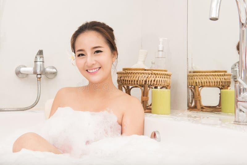 Χαλάρωση γυναικών λουσίματος στη χαλάρωση χαμόγελου λουτρών Ασιατική νέα γυναίκα στην μπανιέρα στοκ εικόνα με δικαίωμα ελεύθερης χρήσης