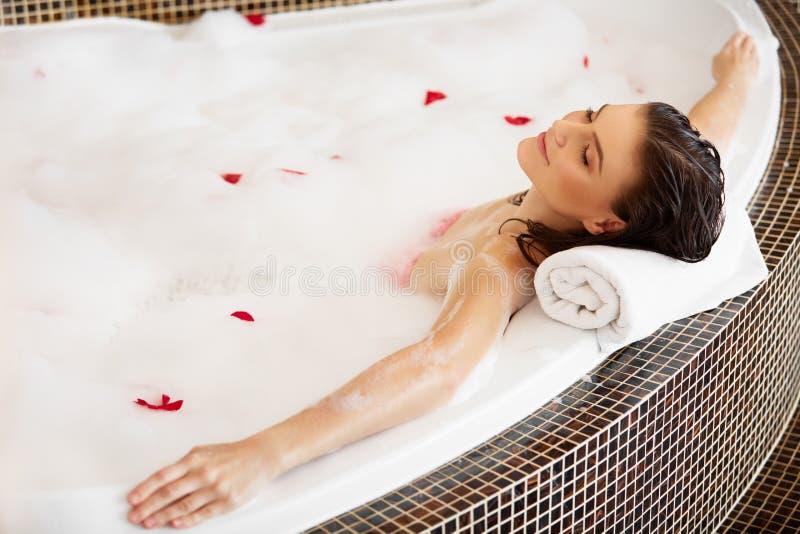 Χαλάρωση γυναικών στο λουτρό φυσαλίδων με τα ροδαλά πέταλα γυναίκα ύδατος σωμάτων care foot health spa στοκ εικόνα