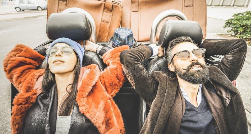 Χαλάρωση ζευγών μόδας hipster στο ταξίδι αυτοκινήτων στο δρόμο στοκ εικόνα
