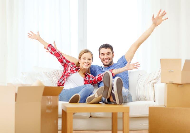 Χαλάρωση ζευγών χαμόγελου στον καναπέ στο νέο σπίτι στοκ εικόνες