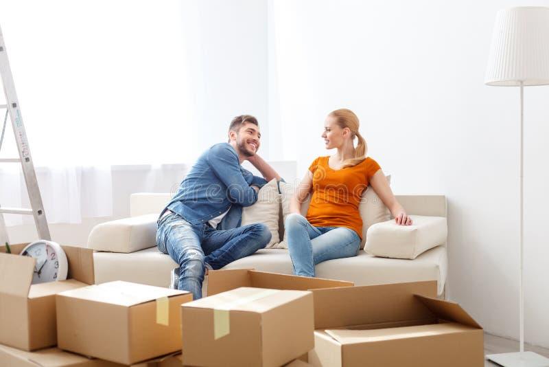 Χαλάρωση ζευγών χαμόγελου στον καναπέ στο νέο σπίτι στοκ φωτογραφία με δικαίωμα ελεύθερης χρήσης