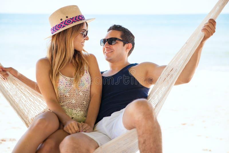 Χαλάρωση ζεύγους σε μια αιώρα στην παραλία στοκ φωτογραφία