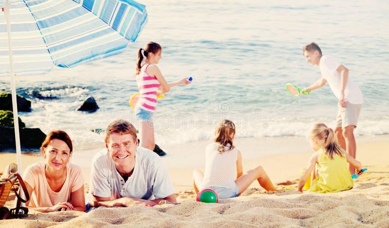 Χαλάρωση ζεύγους στην παραλία ενώ τα παιδιά τους που παίζουν τα ενεργά παιχνίδια στοκ φωτογραφίες με δικαίωμα ελεύθερης χρήσης