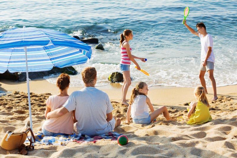 Χαλάρωση ζεύγους στην παραλία ενώ τα παιδιά τους που παίζουν τα ενεργά παιχνίδια στοκ φωτογραφίες