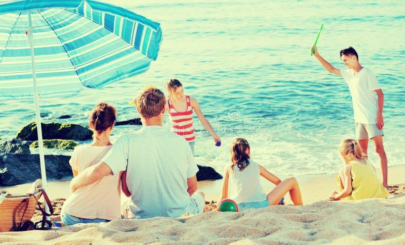 Χαλάρωση ζεύγους στην παραλία ενώ τα παιδιά τους που παίζουν τα ενεργά παιχνίδια στοκ εικόνες με δικαίωμα ελεύθερης χρήσης