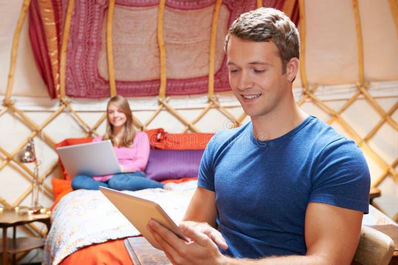 Χαλάρωση ζεύγους στις διακοπές Yurt με τις ψηφιακές συσκευές στοκ φωτογραφία με δικαίωμα ελεύθερης χρήσης