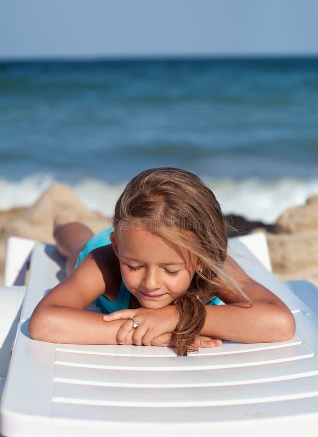 Χαλάρωση μικρών κοριτσιών σε μια καρέκλα παραλιών στοκ φωτογραφίες
