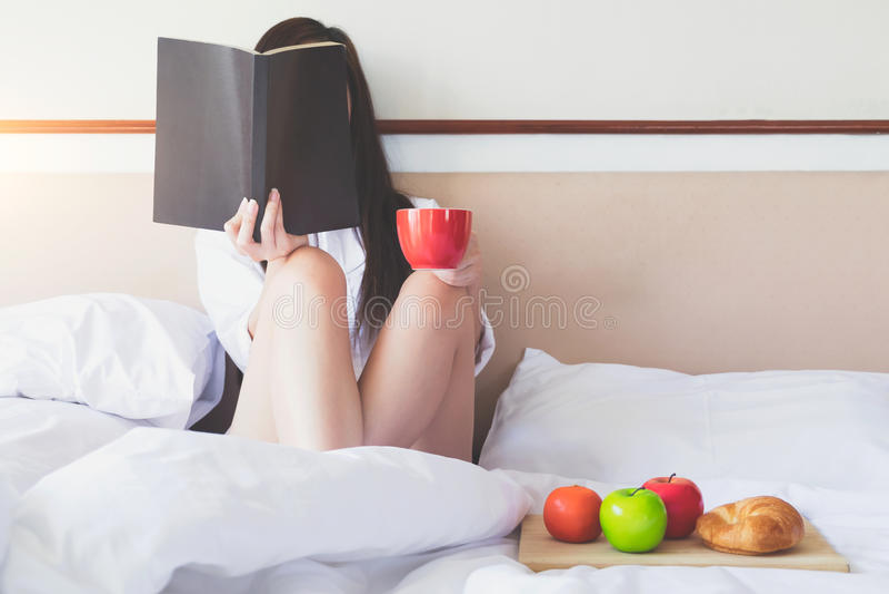 Χαλάρωση το πρωί που διαβάζει ένα βιβλίο και που έχει το πρόγευμα στοκ εικόνες