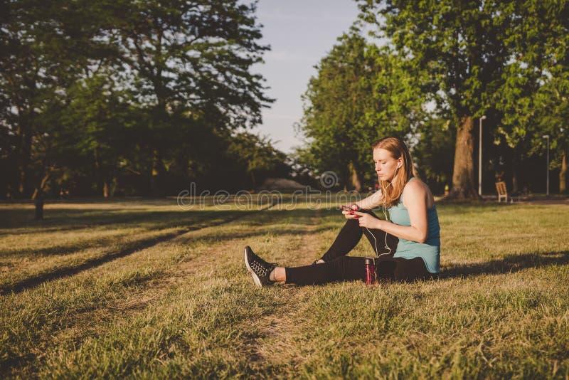 Χαλάρωση υπαίθρια Νέα συνεδρίαση γυναικών στη μουσική πάρκων και ακούσματος στο smartphone της στοκ φωτογραφία με δικαίωμα ελεύθερης χρήσης