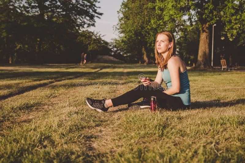 Χαλάρωση υπαίθρια Νέα συνεδρίαση γυναικών στη μουσική πάρκων και ακούσματος στο smartphone της στοκ εικόνα