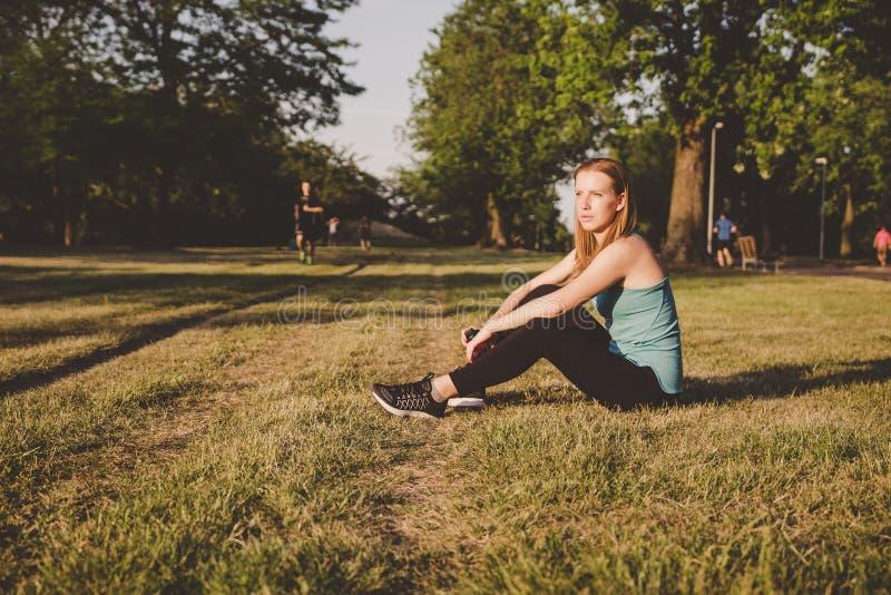Χαλάρωση υπαίθρια Νέα συνεδρίαση γυναικών στο πάρκο και χαλάρωση μετά από να τρέξει στοκ φωτογραφία