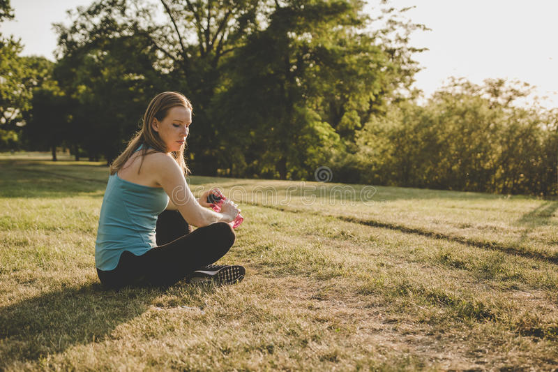 Χαλάρωση υπαίθρια Νέα συνεδρίαση γυναικών στο πάρκο και χαλάρωση μετά από να τρέξει στοκ φωτογραφίες με δικαίωμα ελεύθερης χρήσης