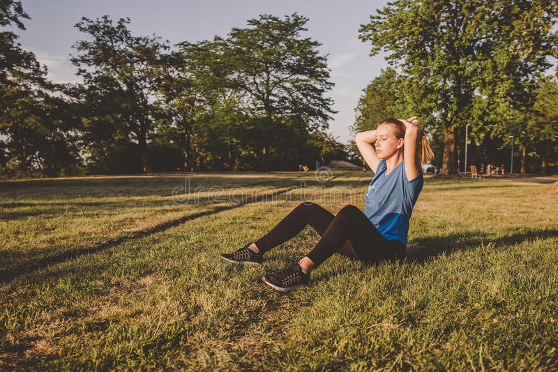 Χαλάρωση υπαίθρια Νέα συνεδρίαση γυναικών στο πάρκο και χαλάρωση μετά από να τρέξει στοκ εικόνες