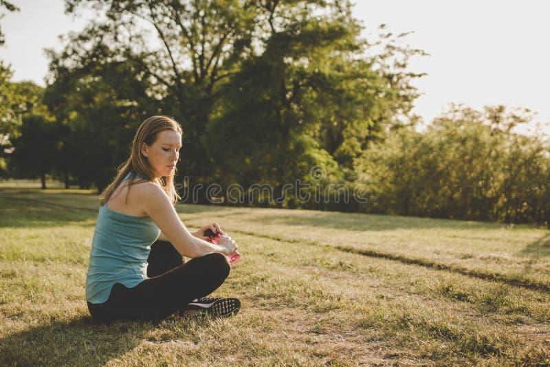 Χαλάρωση υπαίθρια Νέα συνεδρίαση γυναικών στο πάρκο και χαλάρωση μετά από να τρέξει στοκ φωτογραφία με δικαίωμα ελεύθερης χρήσης