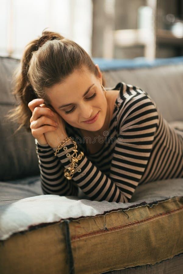 Χαλαρωμένη γυναίκα που βάζει στο ντιβάνι στο διαμέρισμα σοφιτών στοκ φωτογραφία