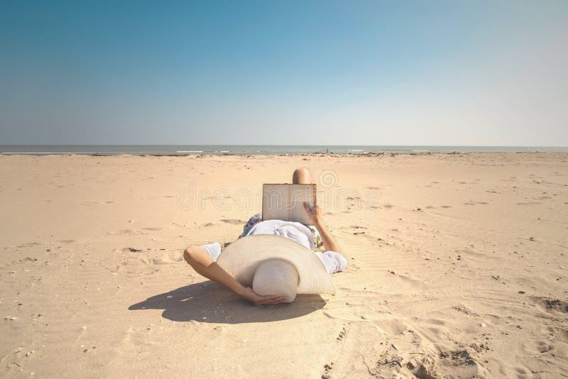 Χαλαρωμένη γυναίκα που διαβάζει ένα βιβλίο μπροστά από τη θάλασσα στοκ φωτογραφία με δικαίωμα ελεύθερης χρήσης