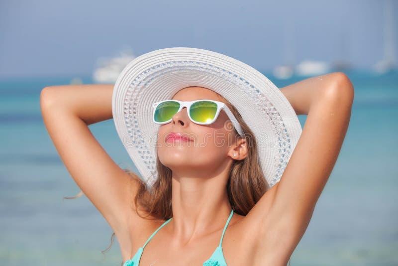 Χαλαρωμένη γυναίκα στην ηλιοφάνεια στην παραλία στοκ φωτογραφία