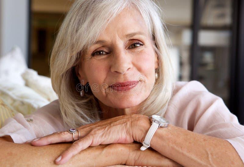 Χαλαρωμένη ηλικιωμένη γυναίκα που χαμογελά και που κάθεται στον καναπέ στοκ φωτογραφία