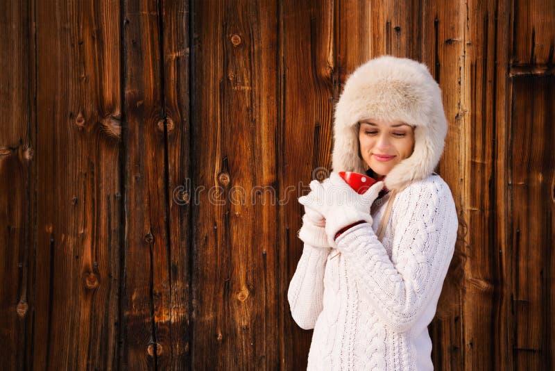 Χαλαρωμένη και ονειροπόλος γυναίκα με το κόκκινο φλυτζάνι κοντά στον αγροτικό ξύλινο τοίχο στοκ εικόνες