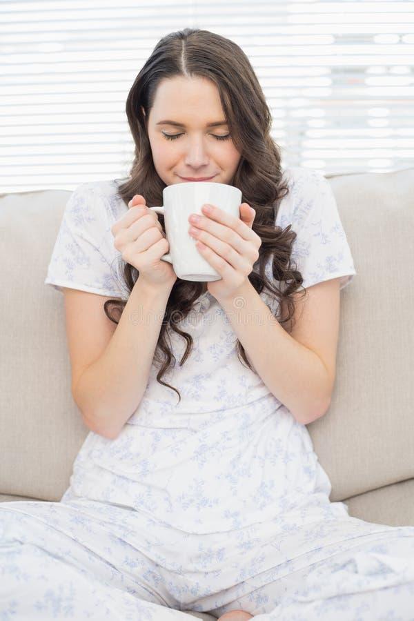 Χαλαρωμένη νέα γυναίκα στις πυτζάμες που έχουν τον καφέ στοκ φωτογραφία με δικαίωμα ελεύθερης χρήσης
