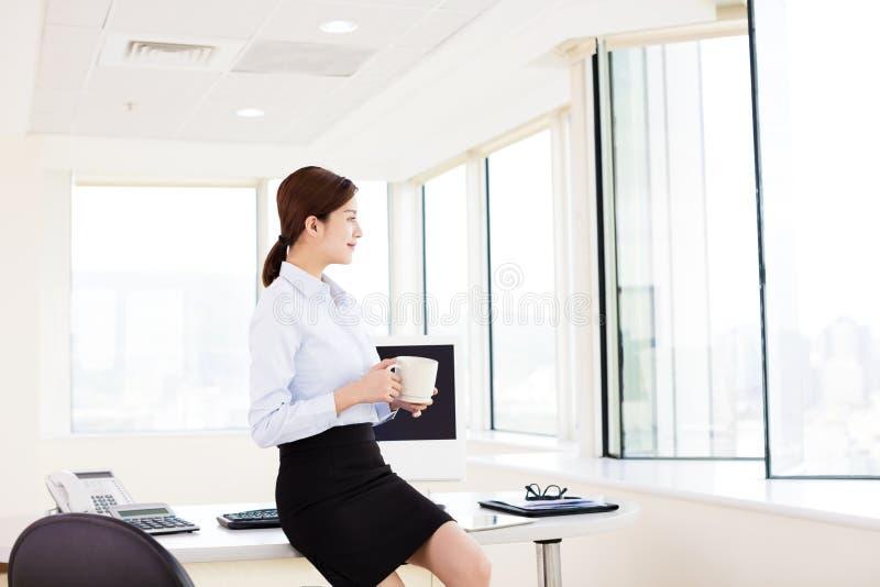 Χαλαρωμένη νέα επιχειρησιακή γυναίκα στο γραφείο στοκ φωτογραφία