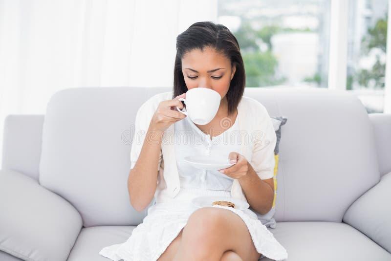 Χαλαρωμένη νέα μελαχροινή μαλλιαρή γυναίκα στα άσπρα ενδύματα που απολαμβάνει τον καφέ και τα μπισκότα στοκ φωτογραφίες