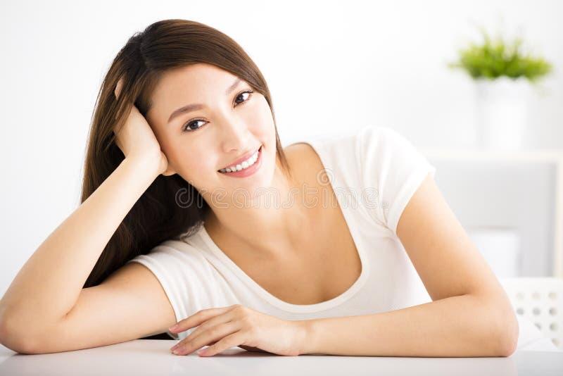 Χαλαρωμένη νέα χαμογελώντας γυναίκα στο καθιστικό στοκ φωτογραφίες