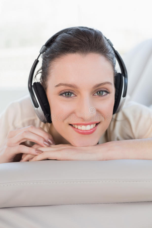 Χαλαρωμένη περιστασιακή νέα γυναίκα που απολαμβάνει τη μουσική στον καναπέ στοκ φωτογραφίες
