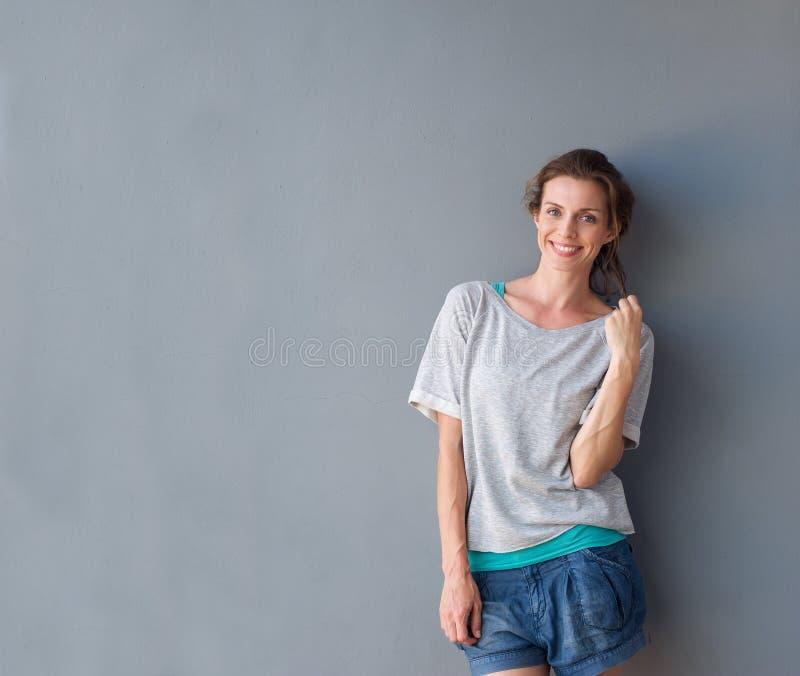 Χαλαρωμένη όμορφη γυναίκα που χαμογελά στο γκρίζο κλίμα στοκ φωτογραφία με δικαίωμα ελεύθερης χρήσης