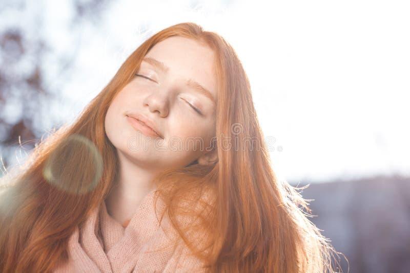 Χαλαρωμένη redhead γυναίκα που στέκεται υπαίθρια στοκ φωτογραφία με δικαίωμα ελεύθερης χρήσης
