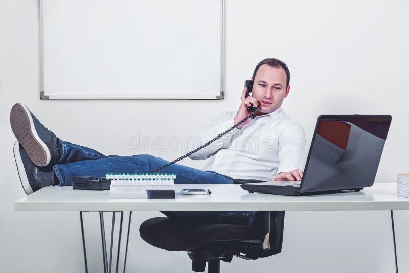 Χαλαρωμένος επιχειρηματίας με τα πόδια στον πίνακα που μιλά στο τηλέφωνο στοκ φωτογραφία